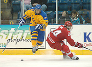 Lake Superior State Laker's Nick McParland uses some fancy footwork to keep the puck away from OSU's Shane Sims during round one of the CCHA playoffs at Taffy Abel Arena.