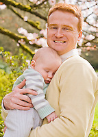A portrait of a father with his 10 month old son outdoors in a Spring like location.