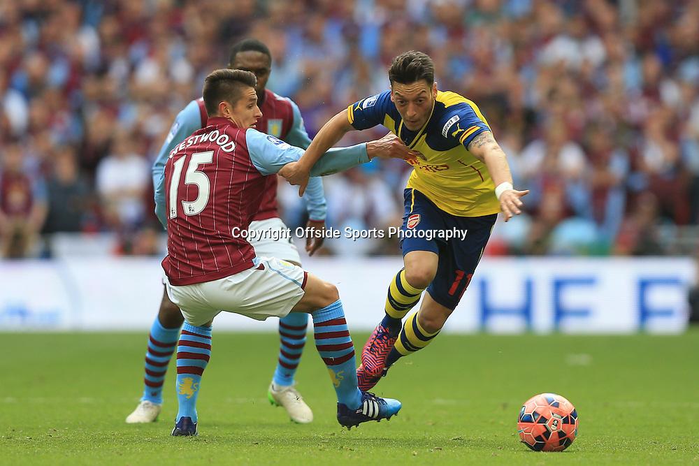 30 May 2015 -FA Cup Final 2015 - Aston Villa v Arsenal - Mesut Ozil of Arsenal tangles with Ashley Westwood of Aston Villa - Photo: Marc Atkins / Offside.