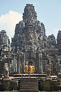 Theravada monks enter Angkor Thom temple in Siem Reap, Cambodia. Enigmatic Buddha faces are carved into the rock walls peering down at those who enter the temple grounds.