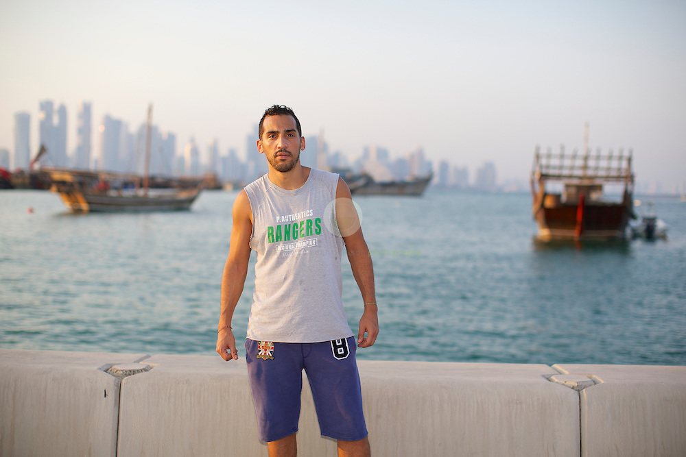 Doha, September 20, 2013<br /> <br /> Zahir Belounis is a French professional footballer currently trapped in Qatar under its controversial labour laws.<br /> <br /> The 33-year-old has not been allowed back to France since June 2012 because he has been embroiled in a legal dispute with his former club al-Jaish, who play in the Qatar Stars League, over two years' unpaid wages.<br /> <br /> Under the Kafala system that ties employees to their sponsors, migrant workers cannot leave the Gulf state unless their employer agrees and Belounis has been left in limbo in Doha with his wife and two daughters. <br /> <br /> They are staying in an half-emply house, as most of his furniture was sold when he got word in that a solution is close. But no progress has been made since then. In November 2013, Belounis has written an impassioned plea to the former 2022 World Cup ambassadors Zinedine Zidane and Pep Guardiola asking them to intervene on his behalf, published by The Guardian newspaper.<br /> <br /> Belounis is shown here at the Doha corniche, with traditional boats (dhows) and the modern skyline in the background.