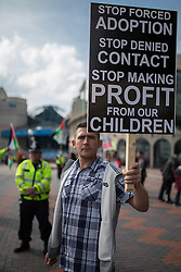"""© Licensed to London News Pictures . 28/09/2014 . Birmingham , UK . Demonstrator with placard reading """" Stop forced adoption stop denied contact stop making profit from our children """" outside the ICC . The 2014 Conservative Party Conference at the International Convention Centre in Birmingham . Photo credit : Joel Goodman/LNP"""