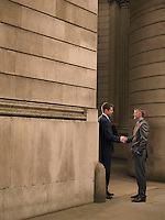 Two businessmen shaking hands at entrance of monumental building