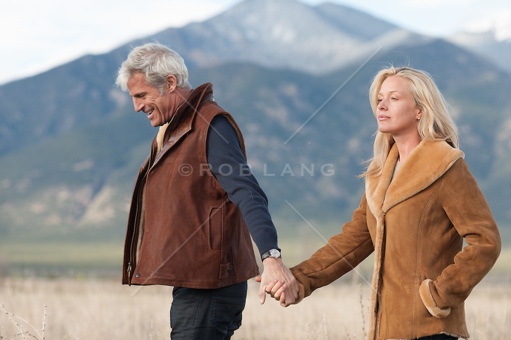 All American couple walking outdoors in beautiful coats