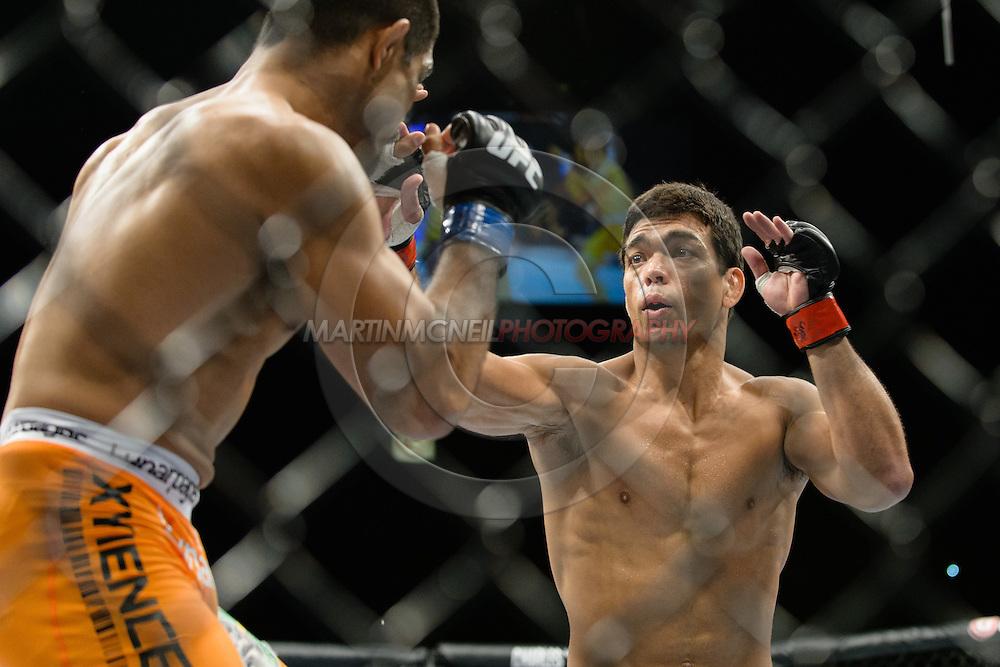 "MANCHESTER, ENGLAND, OCTOBER 26, 2013: Lyoto Machida (black shorts) and Mark Munoz (orange trunks) compete during ""UFC Fight Night 30: Machida vs. Munoz"" inside Phones4U Arena in Manchester, England (© Martin McNeil)"