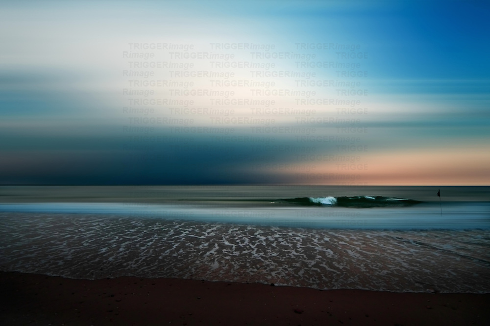 Conceptual beach scene with waves and flag