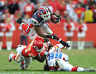 Running back Fred Jackson #22 of the Buffalo Bills leaps over teammate Jonathan Stupar #88 and defender Donald Washington #27 of the Kansas City Chiefs for a first down, during the fourth quarter at Arrowhead Stadium in Kansas City, Missouri. ..