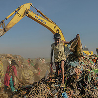 Young and grown up people all working together in a dump yard in outskirt of Dhaka, Bangladesh.<br /> <br /> Their painstaking search amidst the piles of soggy waste, to find pieces of saleable junk, will ensure them two meals a day. These children do not have the luxury of staying away from the waste dump and going to school like other children of their age. Their gruelling labour helps to supplement their parents&rsquo; incomes.