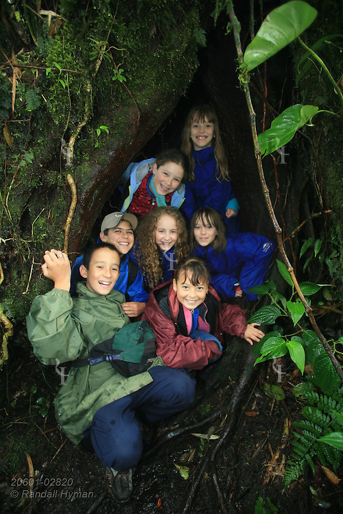 American Ecoteach kids and Cloud Forest School students pose inside tree trunk during nature hike in Santa Elena National Park, Costa Rica.
