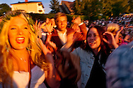 People dancing &quot;the frog dance&quot; jumping around the may pole, during Midsummer night celebrations, Leksand, Sweden<br /> <br /> Midsummer  is one of the most important holidays of the year in Sweden, and probably the most uniquely Swedish in the way it is celebrated. The celebrations in the villages around the city Leksand go on for numerous days, with village parties, dancing and the raising of maypoles.
