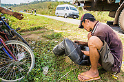 12 MARCH 2013 - ALONG HIGHWAY 13, LAOS:  A man fixes a flat on truck along the side of Highway 13. The truck was hauling raw materials for brooms to China. The paving of Highway 13 from Vientiane to near the Chinese border has changed the way of life in rural Laos. Villagers near Luang Prabang used to have to take unreliable boats that took three hours round trip to get from the homes to the tourist center of Luang Prabang, now they take a 40 minute round trip bus ride. North of Luang Prabang, paving the highway has been an opportunity for China to use Laos as a transshipping point. Chinese merchandise now goes through Laos to Thailand where it's put on Thai trains and taken to the deep water port east of Bangkok. The Chinese have also expanded their economic empire into Laos. Chinese hotels and businesses are common in northern Laos and in some cities, like Oudomxay, are now up to 40% percent. As the roads are paved, more people move away from their traditional homes in the mountains of Laos and crowd the side of the road living off tourists' and truck drivers.    PHOTO BY JACK KURTZ