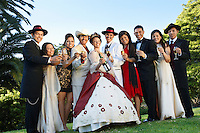 Group portrait of wedding couple and guests in garden