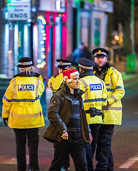 "© Licensed to London News Pictures . 15/12/2017. Manchester, UK. A man wearing a Santa hat and smoking a cigarette walks along Canal Street . Revellers out in Manchester City Centre overnight during "" Mad Friday "" , named for historically being one of the busiest nights of the year for the emergency services in the UK . Photo credit: Joel Goodman/LNP"