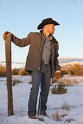 cowboy on a ranch leaning on a fence post at sunset
