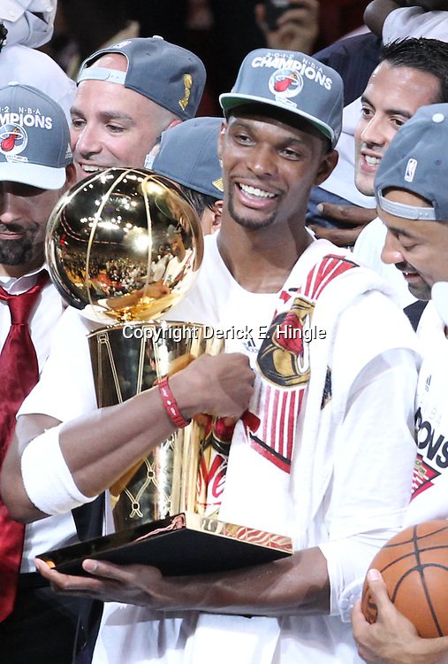 Jun 21, 2012; Miami, FL, USA; Miami Heat power forward Chris Bosh (1) celebrates with the Larry O'Brien trophy after winning the 2012 NBA championship at the American Airlines Arena. Miami won 121-106. Mandatory Credit: Derick E. Hingle-US PRESSWIRE