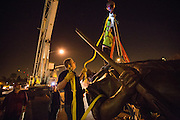 Workers attach ratchet straps to the 12-foot Milpitas Minute Man sculpture to lift it into place with a crane, outside Milpitas City Hall in Milpitas, California, on January 24, 2014. (Stan Olszewski/SOSKIphoto)