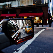 A taxi seen in the mirror of a car