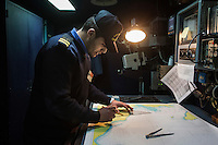 "VALLETTA, MALTA - 8 FEBRUARY 2017: A petty official of the Libyan Navy Coastguard studies a map of the Mediterranean Sea  in the pilot house of the San Giorgio, an amphibious transport dock of the Italian Navy, as it sets out of the harbor of Valetta, Malta, on Febuary 8th 2017.<br /> <br /> As a consequence of the April 2015 Libya migrant shipwrecks, the EU launched a military operation known as European Union Naval Force Mediterranean (EUNAVFOR Med), also known as Operation Sophia, with the aim of neutralising established refugee smuggling routes in the Mediterranean. The aim of this new operation launched by Europe is to undertake systematic efforts to identify, capture and dispose of vessels as well as enabling assets used or suspected of being used by migrant smugglers or traffickers. On 20 June 2016, the Council of the European Union extended Operation Sophia's mandate reinforcing it by supporting the training of the Libyan coastguard.<br /> Thus far, following EUNAVFOR MED operation Sophia's activities, 101 suspected smugglers and traffickers have been apprehended and transferred to the Italian<br /> authorities and 380 boats were removed from the criminal organizations' availability. The Operation has saved 32.081 migrants, among whom 1888 children.<br /> <br /> On February 2nd 2017 Italian Premier Paolo Gentiloni and Prime Minister of the U.N. backed Libyan government Fayez al-Serraj signed a memorandum of understanding on cooperation to combat illegal migration, human trafficking and contraband and on reinforcing the border between Libya and Italy. The following day, as EU leaders meet in Malta for a summit, European Council President Donald Tusk said after talks with Serraj, that ""it is time to close the (migrant) route from Libya to Italy"" and that ""the EU has shown it is able to close the routes of irregular migration, as it has done in the eastern Mediterranean.""  Tusk said the Central Mediterranean route was ""not sustainable either for the EU or for Libya"", where he said"
