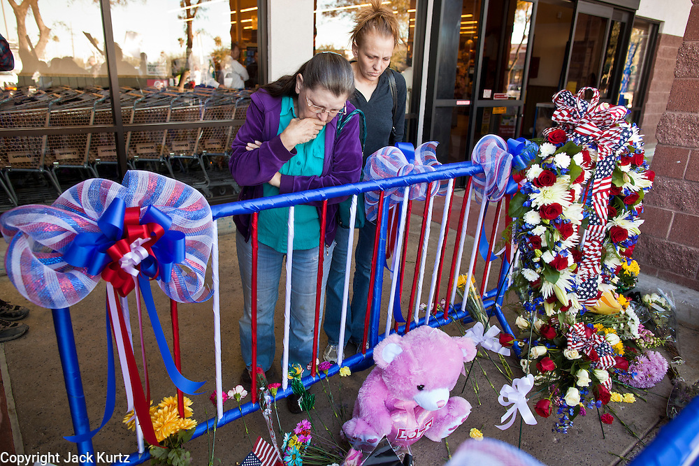 "15 JANUARY 2010 - TUCSON, AZ:    People visit the memorial for victims of the mass shooting in Tucson, AZ, Saturday, January 15. Six people were killed and 14 injured in the shooting spree at a ""Congress on Your Corner"" event hosted by Arizona Congresswoman Gabrielle Giffords at a Safeway grocery store in north Tucson on January 8. Congresswoman Giffords, the intended target of the attack, was shot in the head and seriously injured in the attack but is recovering. Doctors announced that they removed her breathing tube Saturday, one week after the attack. The alleged gunman, Jared Lee Loughner, was wrestled to the ground by bystanders when he stopped shooting to reload the Glock 19 semi-automatic pistol. Loughner is currently in federal custody at a medium security prison near Phoenix.   PHOTO BY JACK KURTZ"