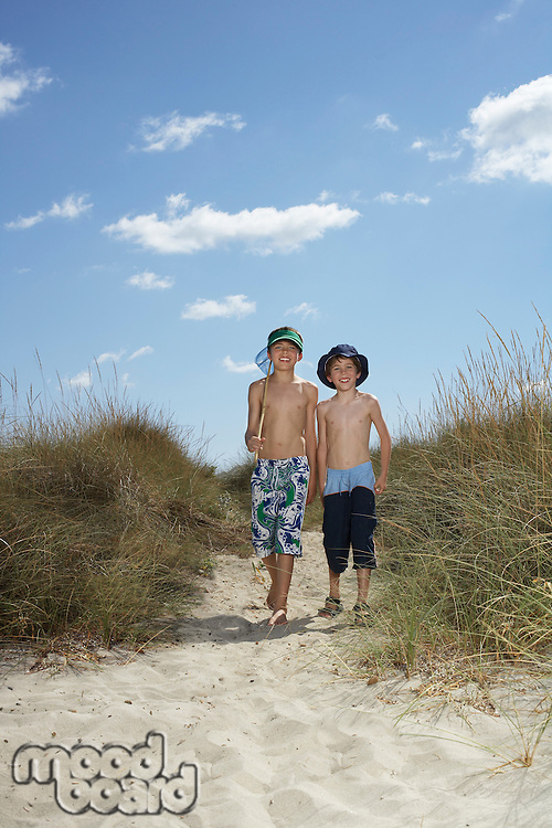 Two boys (6-11) walking in sand dunes with fishing net
