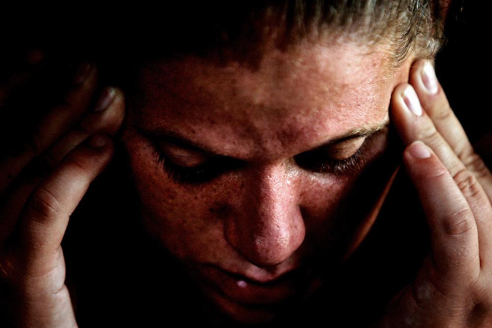 After searching through the newspaper classifieds, Jennifer Audette complains of a headache while massaging her head, as she waits for her boyfriend Chad Perillard to finish a plumbing job. Greg Kahn/Staff.