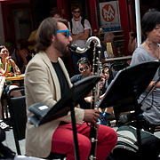 """June 21, 2014 - New York, NY : <br /> The city was flooded with music on Saturday as Make Music New York brought more than 1,300 free concerts to the city's streets and parks. The annual festival's program included the performance """"'In (Key)' - New Compositions in Celebration of Terry Riley's 'In C' @ 50 Years"""" on Cornelia Street, in front of the Cornelia Street Cafe in Greenwich Village, on Saturday afternoon. Spectators found spots on the curb, and at tables at the Cornelia Street Cafe, to catch the show. <br /> CREDIT: Karsten Moran for The New York Times"""