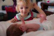 3 year old sister gazes at her newborn baby brother