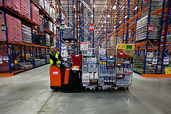 © Licensed to London News Pictures. 25/06/2013. London, UK. A Sainsbury's employee uses a motorised pallet truck in the supermarket chain's newest state of the art logistics centre in Charlton, London, today (25/06/2013). Officially opened today, the logistics centre is currently responsible for supplying around 90 supermarkets in the South East and has so far created 60 jobs on site, with another 1000 to follow in the next three years. Photo credit: Matt Cetti-Roberts/LNP
