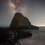 The milky way galaxy shines above the monolith at the tip of Panther Beach in Davenport, CA.
