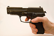 A side view of a male hand holding a Czech CZ-99 9mm parabelum semi-automatic hand gun finger on trigger, Cut out on white background