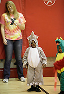 Middletown, New York  - A female volunteer watches children in costumes play games in the gymnasium during the Middletown YMCA Family Fall Festival on Oct. 29, 2011. ©Tom Bushey / The Image Works