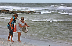 October 7, 2016 - Treasure Island, Florida, U.S. - SCOTT KEELER       Times. Left to Right: Visitors Staci Devick, Reinbeck, Iowa and Debbie Barber, La Porte City, Iowa, look for shells on Sunset Beach, Treasure Island in a stiff northwest wind from Hurricane Matthew, Friday, 10/7/16. Both said the shelling was good from the large waves. (Credit Image: © Scott Keeler/Tampa Bay Times via ZUMA Wire)