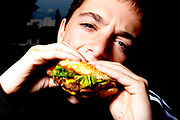 A young boy eating a fast food burger.