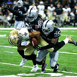 Sep 11, 2016; New Orleans, LA, USA;  New Orleans Saints wide receiver Willie Snead (83) fumbles as he is hit by Oakland Raiders cornerback D.J. Hayden (25) and defensive back Reggie Nelson (27) during the fourth quarter of a game at the Mercedes-Benz Superdome. The Raiders defeated the Saints 35-34. Mandatory Credit: Derick E. Hingle-USA TODAY Sports