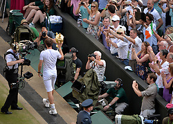 © London News Pictures. 07/07/2013 . London, UK. Andy Murray holding the trophy as he celebrates after his men's singles final victory over Novak Djokovic of Serbia at the Wimbledon Lawn Tennis Championships final, becoming the first British male to win the tournament in 77 years. Photo credit: Mike King/LNP