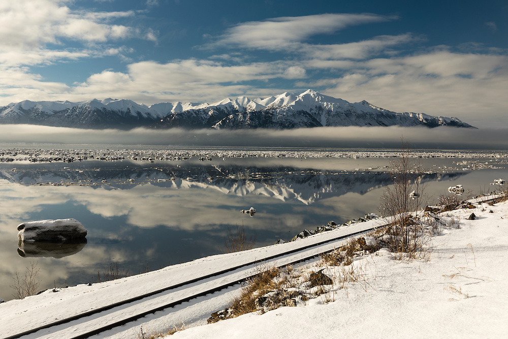 Icebergs break up the reflection of the Kenai Mountains in Turnagain Arm at high tide in Southcentral Alaska. Winter. Afternoon.