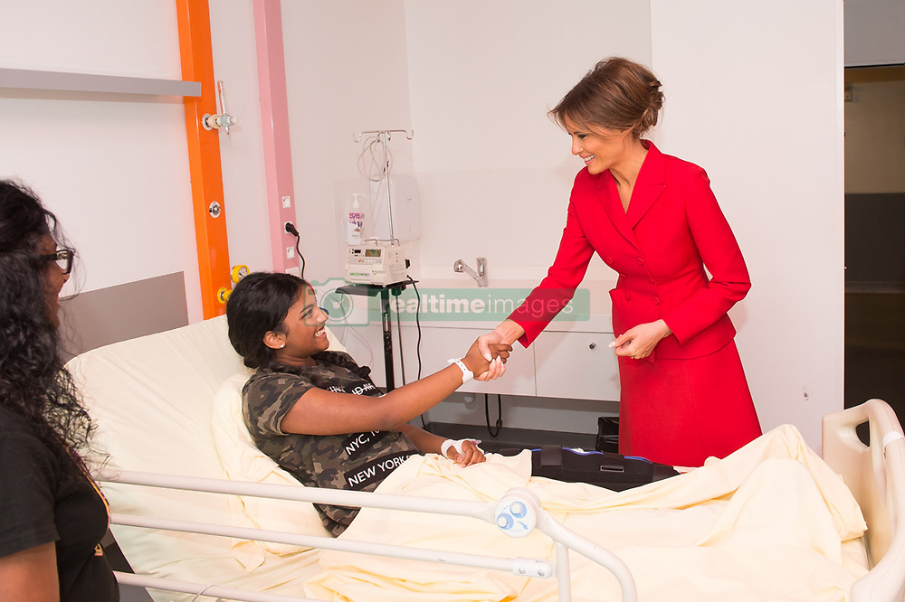 July 13, 2017 - Paris, France - U.S. First Lady Melania Trump greets a young patient during a visit to Necker hospital, the largest pediatric hospital in France July 13, 2017 in Paris, France. The first lady paired a rare updo with a bright red Dior skirt suit and matching red pumps as she set off on her own schedule in Paris prior to Bastille Day celebrations. (Credit Image: © Andrea Hanks/Planet Pix via ZUMA Wire)