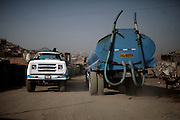 Pipe trucks enter and leave selling water at the human settlement of Laderas del Paraiso, early Monday, April 17, 2011. (Dado Galdieri)