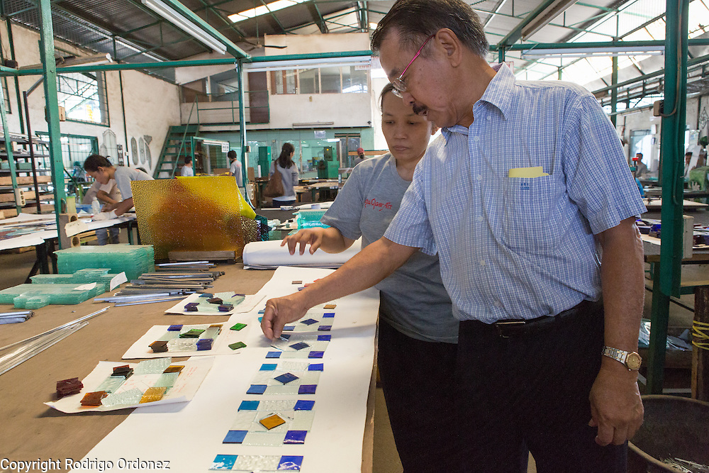 Eztu Glass founder and CEO Brian Yaputra (right) inspects pieces of stained glass at his company's factory in Tangerang, near Jakarta, Indonesia, on July 2, 2015.