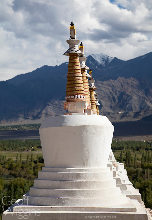 Chortens and spires of Shey Monastery Ladakh, overlooking the Indus River valley and beyond the Zanskar range of hills. Shey, built first in 1655, was the home to the kings of Ladakh and located 15 km. from Leh