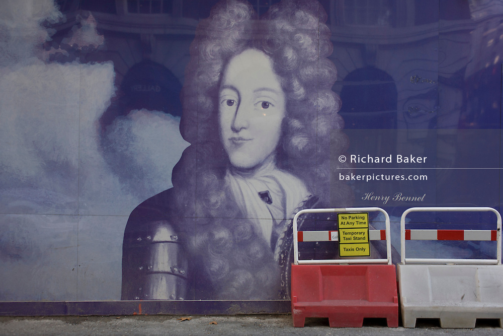 18th century English aristocrat Henry Bennet on a construction hoarding alongside a red standing pedestrian light in central London.