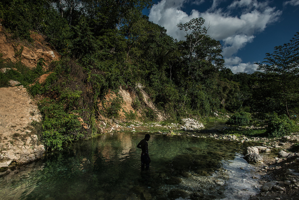 TETE A L'EAU, HAITI - NOVEMBER 22, 2015: A man swims in the river that runs next to Camp Tete A L'eau, near the border line to the Dominican Republic. On this arid strip of borderland, the river brings life. Its languid waters cook the food, quench the thirst and bathe the bodies of thousands of Haitians who poured onto its banks this summer, fleeing threats of violence and deportation from their neighbors in the Dominican Republic.  These days, it is also brings death. Horrid sanitation has lead to a cholera outbreak in the camps, infecting and killing residents. PHOTO: Meridith Kohut for The New York Times