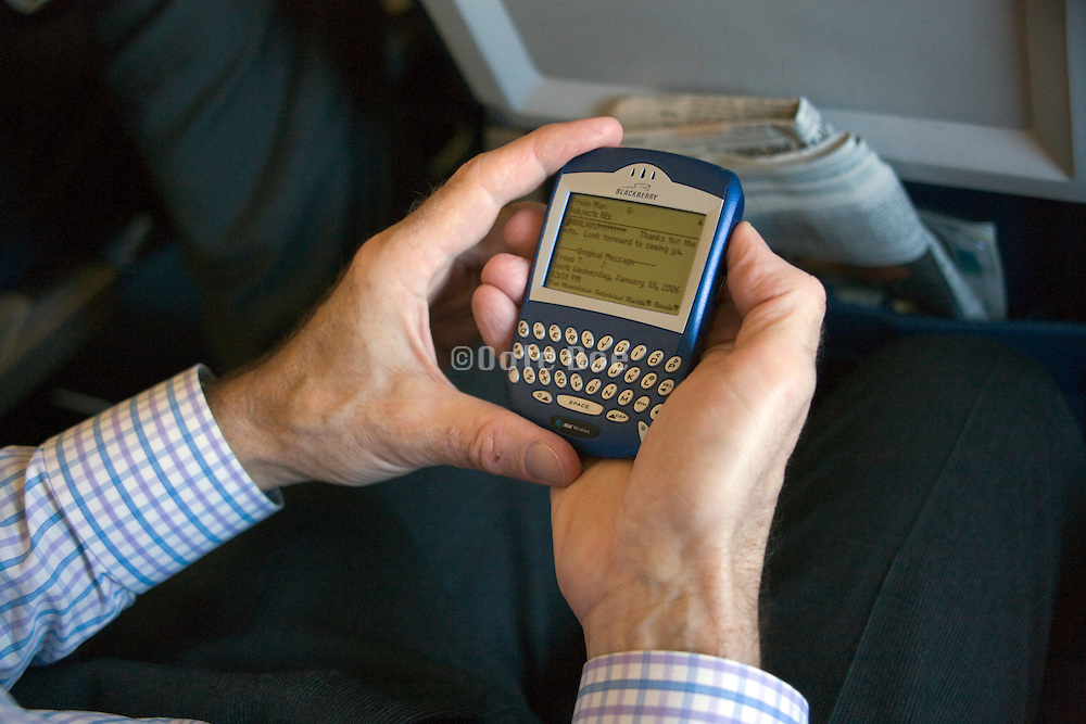 close up of a man working with his Blackberry inside an airplane
