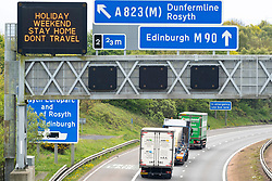 Dunfermline, Scotland, UK. 7 May 2020. Afternoon traffic on M90 in Fife noticeably heavier than normal during coronavirus lockdown. Warning sign telling motorists to stay home over holiday weekend. Iain Masterton/ Alamy Live News.