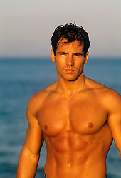 man with a great upper body standing by the ocean