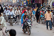 Father with child on motorcycle in crowded street during holy Festival of Shivaratri in city of Varanasi, India