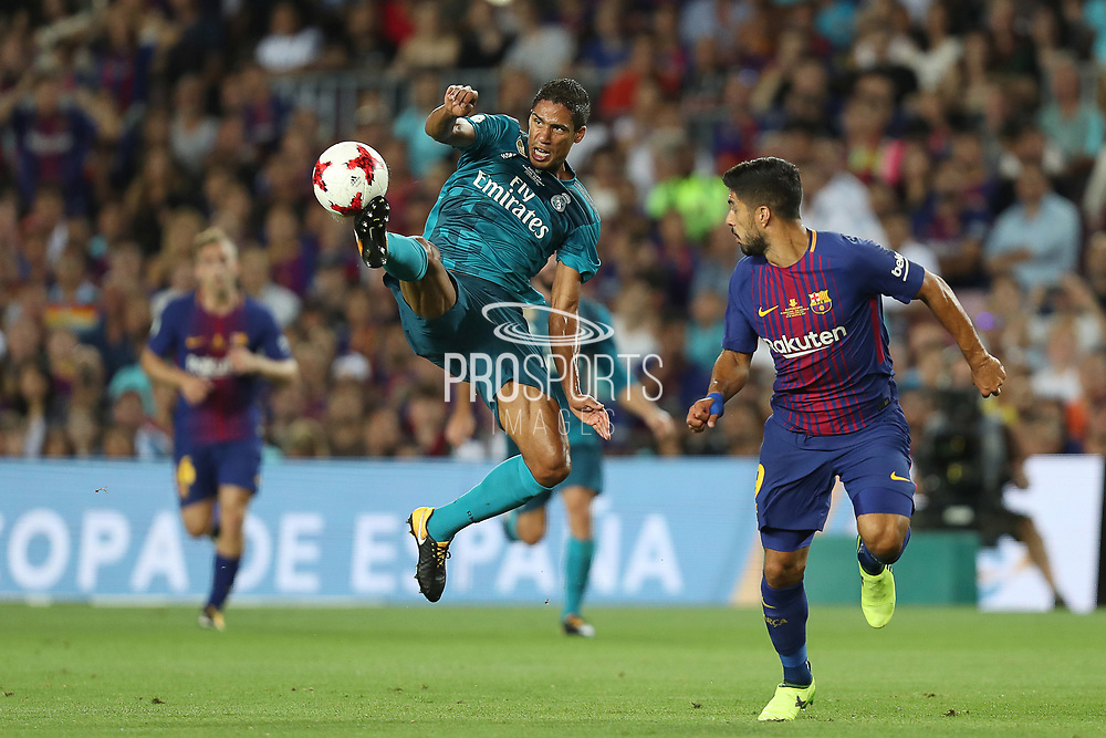 Raphael Varane of Real Madrid controls the ball under pressure from Luis Suarez of FC Barcelona during the Spanish Super Cup football match between FC Barcelona and Real Madrid on August 13, 2017 at Camp Nou stadium in Barcelona, Spain. - Photo Manuel Blondeau / AOP Press / ProSportsImages / DPPI