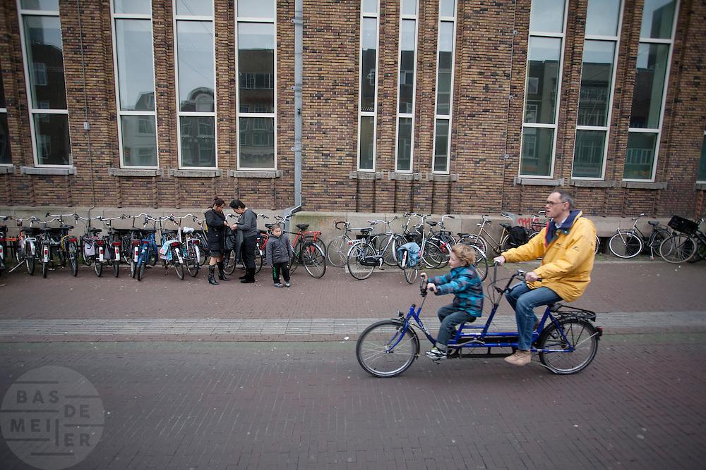 Een man rijdt op een tandem met een kind voorop langs de Neude in Utrecht.<br /> <br /> A man is riding on a tandem in Utrecht.