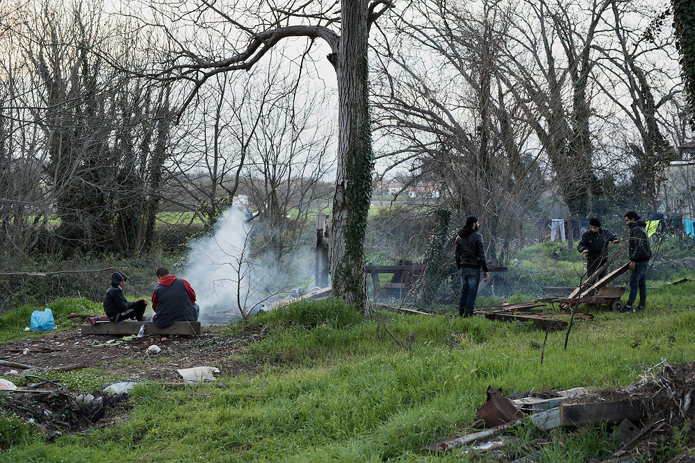 A group of Syrian Kurds is chopping wood and light a fire behind the railway station of Idomeni. <br /> <br /> Thousands of refugees are stranded in Idomeni unable to cross the border. The facilities are stretched to the limit and the conditions are appalling