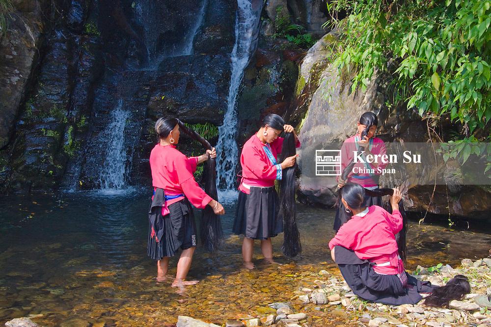 Red Yao girls brushing long hair by the waterfall,  Longsheng, Guangxi, China
